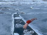 Incredible footage shows a daredevil dressed only in shorts swimming under ice in the Arctic