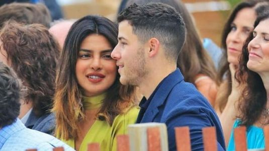 Priyanka Chopra glitters in gold on Nick Jonas's arm at his cousin's wedding